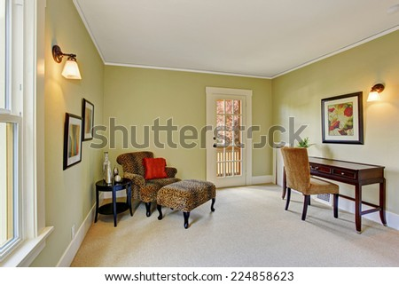 Light green office room with desk and sitting area in the corner with leopard armchair and small table - stock photo