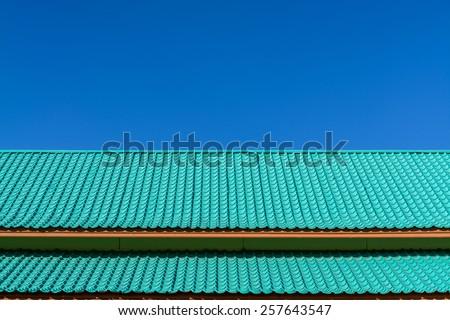 Light green roof tile pattern over blue sky - stock photo