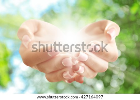 Light in hands on green nature background. Concept of taking care, protection, helping and assistance - stock photo