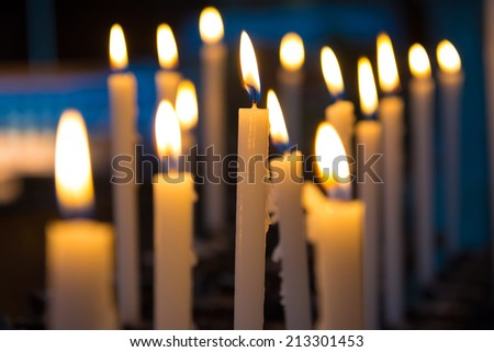 Light of candels in the church on the black background - stock photo
