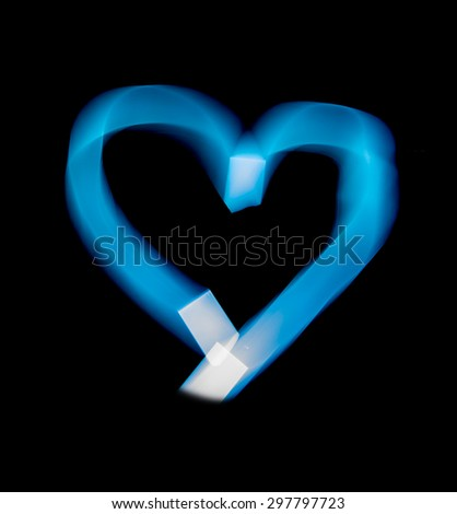 Light of painting the heart shape on black background. - stock photo