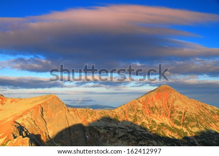 Light of the rising sun touches the mountain top in the morning  - stock photo