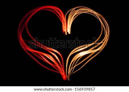 Light painting heart shape over black background - stock photo