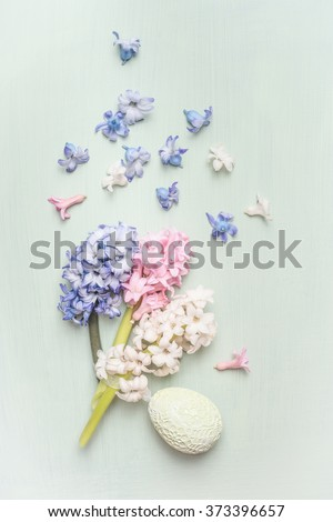Light pastel Easter greeting card with hyacinths flowers and egg, top view - stock photo