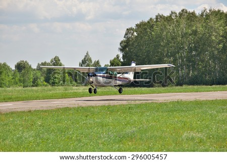 Light plane landing on the runway on the airfield - stock photo