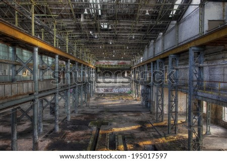 Light rays in a large abandoned production hall with an old crane - stock photo