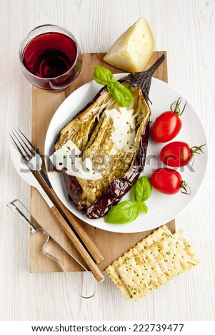 light salad with roasted eggplant and fresh cherry tomato. healthy lunch. italian cheese parmesan and red wine. - stock photo