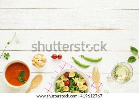 Light summer dinner / supper concept. Green salad with pasta, cherry tomato, quail eggs, olive oil. Cold tomato soup (gazpacho), croutons and glass of cold white wine.  - stock photo