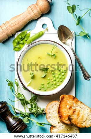 Light summer green pea cream soup in bowl with sprouts, bread toasts and spices. White ceramic board in the center, turquoise blue wooden background. Top view. - stock photo