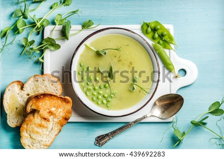 Light summer green pea cream soup in bowl with sprouts, bread toasts and spices. White ceramic board in the center, turquoise blue wooden background. Top view, horizontal - stock photo