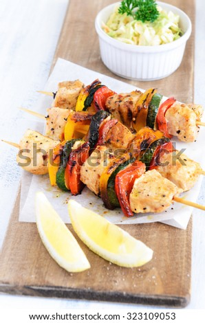 Light summer lunch grilled chicken and vegetable skewers served with coleslaw side salad - stock photo