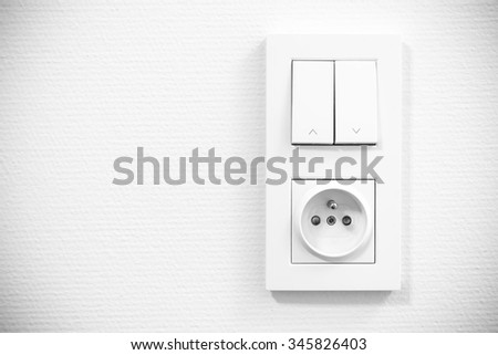 light switch and socket in frame on the wall - stock photo