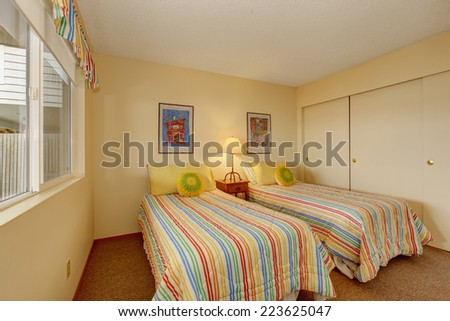 Light tone bedroom with two single beds in cheerful striped bedding with yellow pillows - stock photo