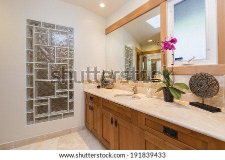 Light tones bathroom with wood cabinets. Decorated with beautiful flowers - stock photo