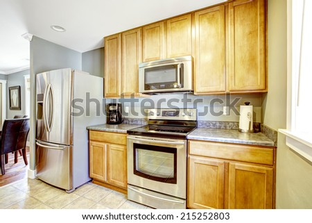 Light tones kitchen cabinets with granite top and steel appliances - stock photo