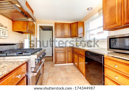 Light tones kitchen room with wood cabinets, modern appliances, tile floor and tile backsplash - stock photo