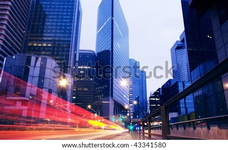Light trails from cars in business centre - stock photo