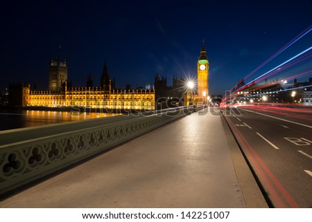 Light trails from London buses and vehicles with the Elizabeth Tower (Big Ben) of the Palace of Westminster in the background and the path on Westminster bridge foreground - stock photo