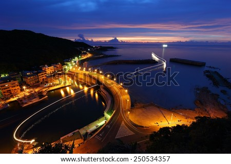 Light trails of boats and dawn with rosy glow. Morning view of a fishing village in northern coast of Taipei Taiwan - stock photo