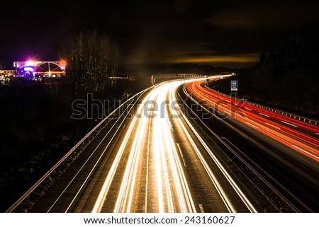 Light trails on a german Autobahn (Highway) at the motorway exit Pfaffenhofen. - stock photo