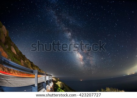Light trails on the road with the milky way galaxy on the sky - stock photo