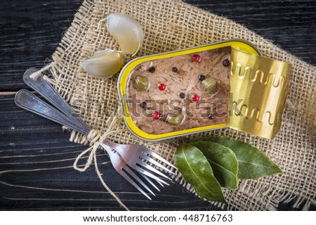"Light tuna in olive oil canned dressed with herbs and spices on a burlap and a wooden background translation ""lift cover and pull"" - stock photo"