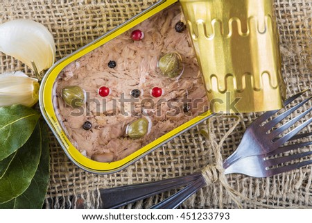 Light tuna in olive oil canned dressed with herbs and spices on a burlap and a wooden background - stock photo