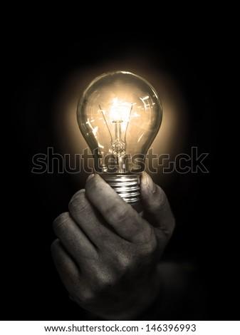 lightbulb hold in hand on black background - stock photo