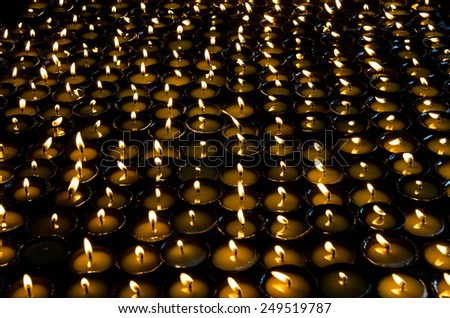 Lighted candles lined up in a row and glow in the dark space. Monastery in Nepal. Tibet, the Himalayas. - stock photo