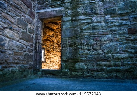 Lighted dorway to the medieval castle - stock photo