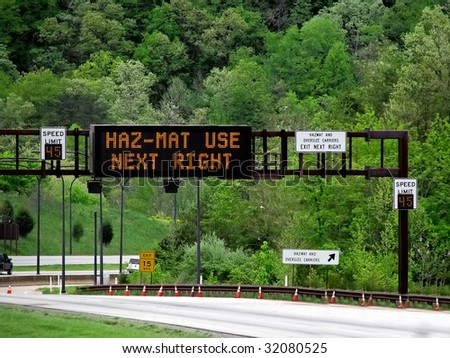 lighted overhead highway sign hazmat use next righ - stock photo