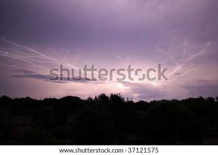Lightening strike over woods and houses - stock photo