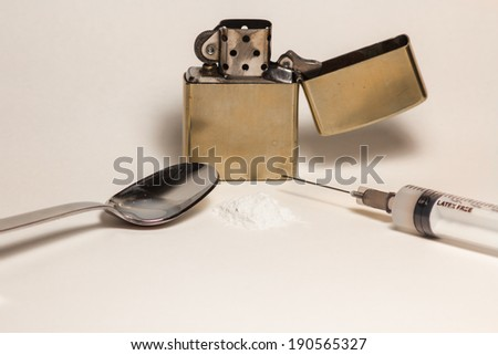 Lighter, spoon and heroin, with a syringe for the injection - stock photo