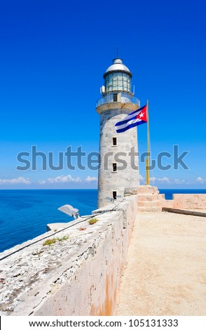 Lighthouse and cuban flag with a beautiful view of the ocean on el Morro castle in Havana - stock photo
