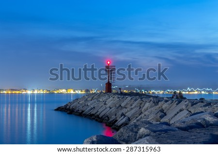 lighthouse and rocks night seascape. City lights after sunset. Rimini Italy - stock photo