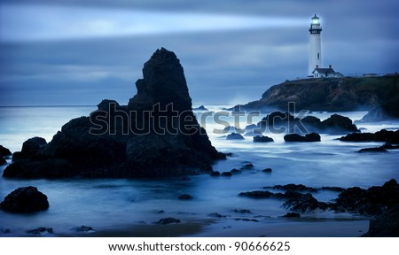 Lighthouse at the California coast with light beam - stock photo