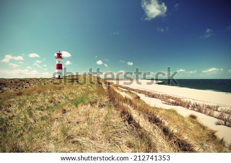 Lighthouse at the German North Sea island Sylt in the dunes at the beach with blue sky, vintage style - stock photo