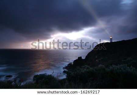 lighthouse at the time of dramatic stormy sunset - stock photo