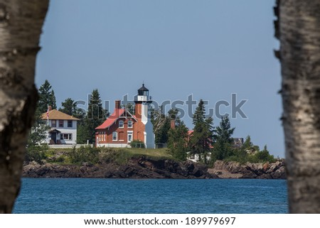 Lighthouse between Trees - Eagle Harbor Lighthouse on Lake Superior in Michigan's Upper Peninsula. - stock photo