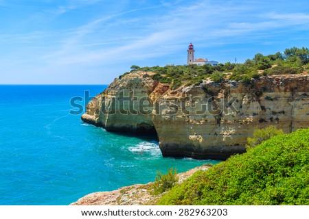 Lighthouse building on top of cliff on coast of Portugal bear Carvoeiro town, Algarve region - stock photo
