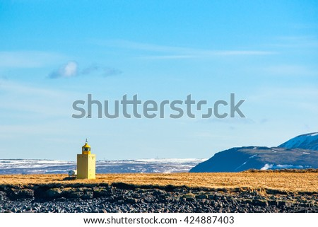 Lighthouse in an icelandic landscape with mountains - stock photo
