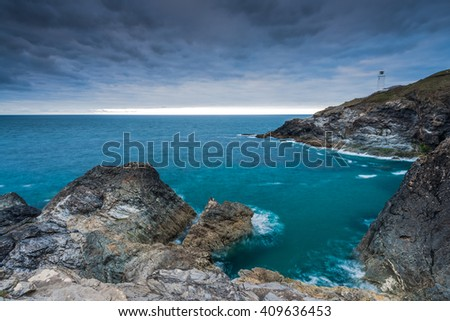 Lighthouse in Cornwall on rocky cliffs with dramatic sky and Atlantic ocean - stock photo