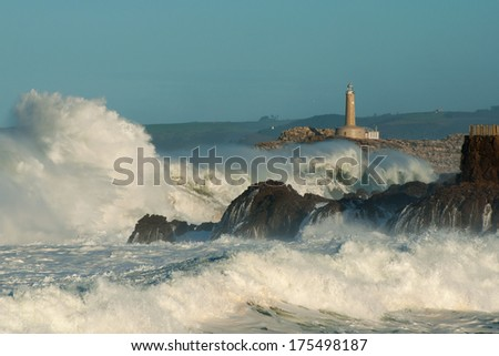 Lighthouse in the big waves, storm in Mouro, Santander, Spain - stock photo