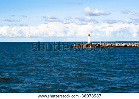 Lighthouse in the middle of sea - stock photo