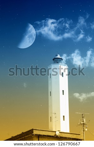 lighthouse in the night with moon in the sky - stock photo
