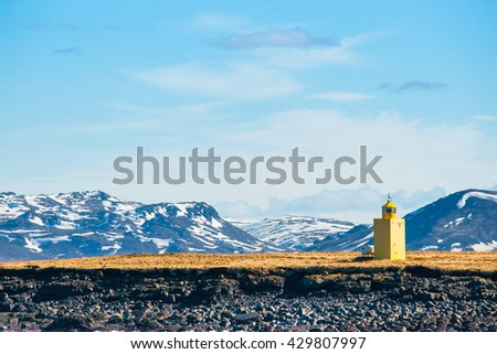 Lighthouse in yellow color in a landscape with mountains - stock photo