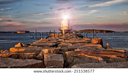 Lighthouse on a rocky ledge at sunset - stock photo