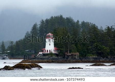 Lighthouse on a rocky shoreline - stock photo