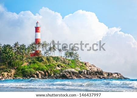 Lighthouse on the rocks near the ocean at blue sky with big white clouds in Kovalam, Kerala, India   - stock photo