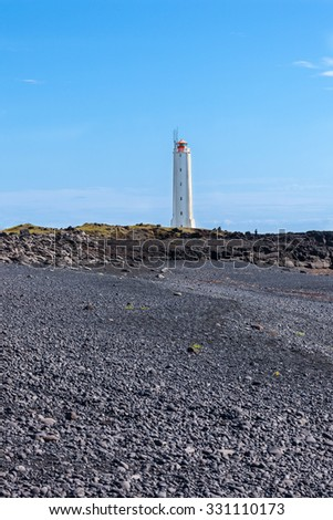 Lighthouse on West Coast of Iceland at sunny weather. Vertical shot - stock photo